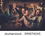 Stock photo cheerful old friends having fun watching a football game on tv and drinking draft beer at bar 390074245