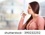 young woman with a glass of... | Shutterstock . vector #390232252