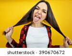 Small photo of Hipster girl in checked shirt showing tongue with piercing over yellow background. Impertinent behaviour. Hipsters. Provocation. Aggression. Naughtiness.