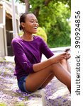 Small photo of Portrait of young african american lady sitting by a street and reading text message on her cell phone