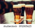 Stock photo glasses of light and dark beer on a pub background 391005625