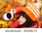 Girl in autumn orange leaves with cup coffee. Outdoor. - stock photo