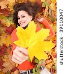 Girl in orange on autumn foliage with yellow leaf.  Outdoor. - stock photo