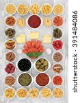 Small photo of Large italian food ingredient sampler with pasta, pesto, ragu, olives, chorizio and garlic over distressed white wood background.