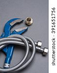 Small photo of Adjustable spanner, nipple, and braided stainless steel water hose over grey background