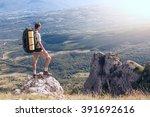 backpacker stands on a high... | Shutterstock . vector #391692616