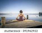 a pretty woman doing yoga at... | Shutterstock . vector #391962922
