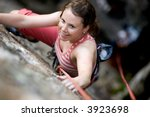 A female climber on a steep rock face viewed from above with the belayer in the background.  The climber is smiling at the camera. Shallow depth of field is used to isolated the climber. - stock photo