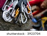 A pile of quick draw carabiners with climbers out of focus in the background. - stock photo