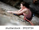 A female climber on a steep rock face.  Shallow depth of field is used to isolated the climber. - stock photo