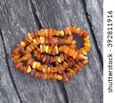 Small photo of Bright orange amber necklace of raw beads/Necklace of amber beads/Amber beads string on an old gray wooden background