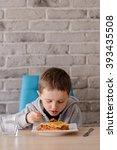 7 years old boy eating lasagne... | Shutterstock . vector #393435508
