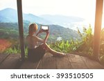 Female traveler is shooting video on portable touch of a wonderful Amazon view during her unforgettable summer weekend. Young woman tourist is taking photo with digital tablet camera of jungle view - stock photo