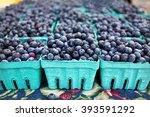 Blueberries in Individual Crates at Farmers Market For Sale farm fresh organic fruit in the summer on Table depth of field - stock photo