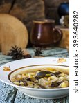 Small photo of traditional Russian cabbage soup shchi with mushrooms in a rustic style