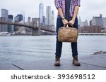 Small photo of Closeup of a young entrepreneur with boots and a briefcase in New York