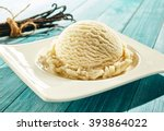 Stock photo single scoop of creamy vanilla ice cream on a stylish modern plate on a blue wooden picnic table 393864022