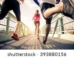 Stock photo three runners sprinting outdoors sportive people training in a urban area healthy lifestyle and 393880156