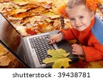Girl child in autumn orange leaves with laptop. Outdoor. - stock photo