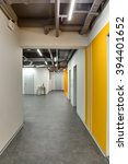 Small photo of Corridor with white walls. Right wall is with orange colored zones and with passages. There are gray doors at the end of corridor. Near the nearer door there are two small tables with plants in the