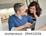 couple at home using laptop... | Shutterstock . vector #394413256