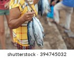 man holding fresh fish by their ... | Shutterstock . vector #394745032
