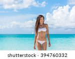 Sexy Asian bikini woman relaxing on beach walking from turquoise ocean water wearing white fashion swimwear. Skin and hair care female model with slim body for weight loss.