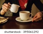 a girl pours milk into coffee... | Shutterstock . vector #395061292