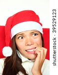 Christmas woman with santa hat nervous biting nails. Beautiful mixed asian / caucasian model. - stock photo