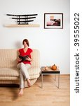 woman is sitting on a sofa at... | Shutterstock . vector #39555022