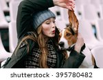Stock photo young hipster girl with her pet estonian hound dog playing and having fun outdoor in the park 395780482
