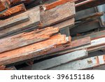 Small photo of Pile of old used timber planks. Old, rotten, scrapped floorboards and decking planks amassed and scattered in a heap.