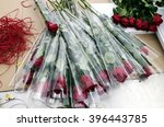 Small photo of Red roses wrapped in cellophane inside a flower market and ready for sale.