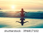 Stock photo female silhouette doing exercise at beautiful sunset on the sea beach yoga fitness and healthy 396817102