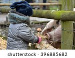 Young Child Feeding Straw To...