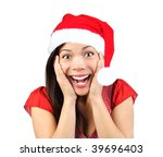 Christmas girl very excited and surprised holding her head. Beautiful mixed asian / caucasian model. Isolated on seamless white background. - stock photo