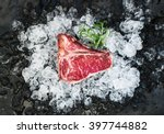 Small photo of Raw fresh meat t-bone steak on chipped ice with rosemary over dark slate stone backdrop, top view. Horizontal