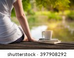 Small photo of Young woman sitting and put down her hand beside coffee cup and notebooks on rustic wood bench with rural lake view in morning time on weekend