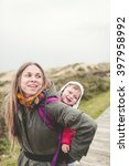mother carrying her child in a... | Shutterstock . vector #397958992