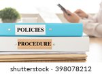 Small photo of Policies and Procedures doucument place on desk in meeting room. Policy, Procedure concept.