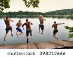Stock photo happy young boys jumping togetherto the calm summer sea adventure team photo on summer holiday or 398212666