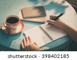 Stock photo woman right hand writing journal on small notebook at outdoor area in cafe with morning scene and 398402185