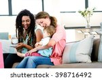 two women sitting on a couch... | Shutterstock . vector #398716492