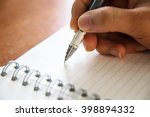 hands with pen writing on a... | Shutterstock . vector #398894332