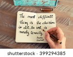 Small photo of Retro effect and toned image of a woman hand writing on a notebook. Handwritten quote The most difficult thing is the decision to act, the rest is merely tenacity. - Amelia Earhart as concept image