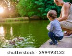 Young pregnant mother walking with her little son in summer park near the lake and feed the ducks