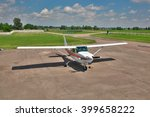 Small photo of Light private plane parked on the apron of an airfield in summer