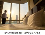 Stock photo bed maid up with white pillows and bed sheets in cozy room young businessman with cup of coffee 399937765