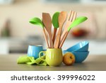 Stock photo set of wooden kitchen utensils in green cup with napkin and dishes on the table 399996022