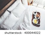 Stock photo breakfast on a tray in bed in hotel white linen wooden interior 400044022